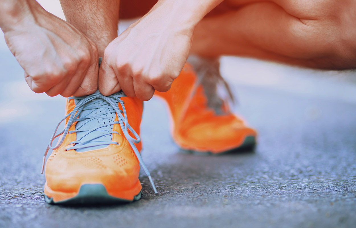 Man gets ready for the run with his orange sports shoes.